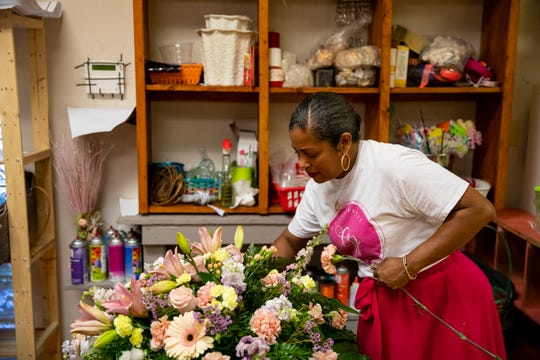 Tyra Craig, owner of Golden Petal Florist, works on a flower arrangement in her store on Thursday, June 11, 2020.