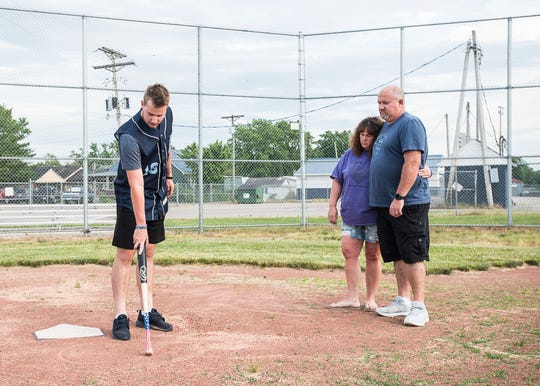 Ethan Kunkel draws his brothers number 18  in the sand to honor his brother Eli while wearing his brother Eli's senior jersey as his parents Corinna and Chuck  watch  at the Adena baseball field a year after his death on June 09, 2020.