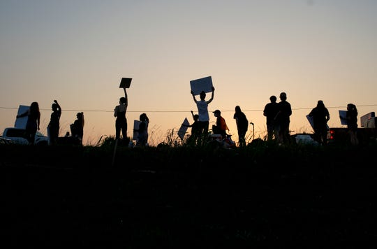 Protesters raise their signs and mingle at the top of a small hill at the sidewalk across from O'Charley's on Wilma Rudolph in Clarksville, Tenn., on Tuesday, June 9, 2020.