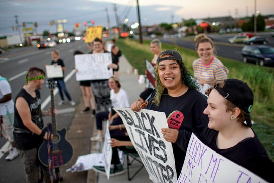 Protesters embrace signs and hang out together during the daily protest at the sidewalk across from O'Charley's on Wilma Rudolph in Clarksville, Tenn., on Wednesday, June 10, 2020.