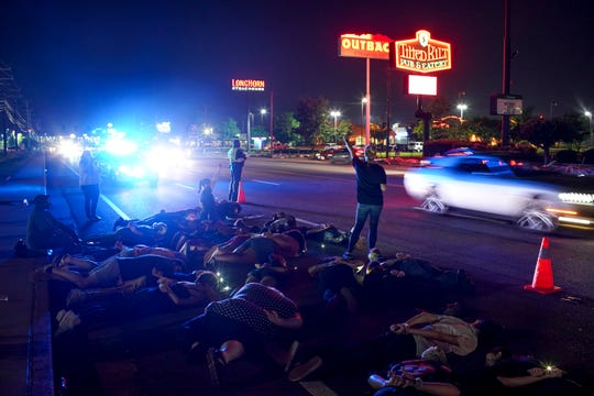 Demonstrators lay down on the first lane of the road for nine minutes for a statement in solidarity at the sidewalk across from O'Charley's on Wilma Rudolph in Clarksville, Tenn., on Tuesday, June 9, 2020.