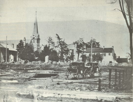 """Rubble from the destruction near Third and Franklin Streets, with Trinity Episcopal Church in the background, after the Great Fire of 1878 in Clarksville, Tenn., from """"Homes & Happenings"""" by Eleanor S. Williams and Ursula S. Beach."""