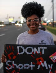 Jayda Nash poses for a portrait with her sign at the sidewalk across from O'Charley's on Wilma Rudolph in Clarksville, Tenn., on Tuesday, June 9, 2020.