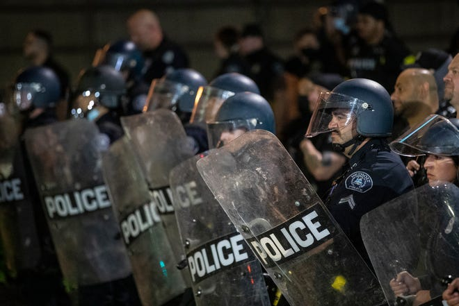 Detroit Police officers in riot gear watch protesters in downtown Detroit, Friday, May 29, 2020.
