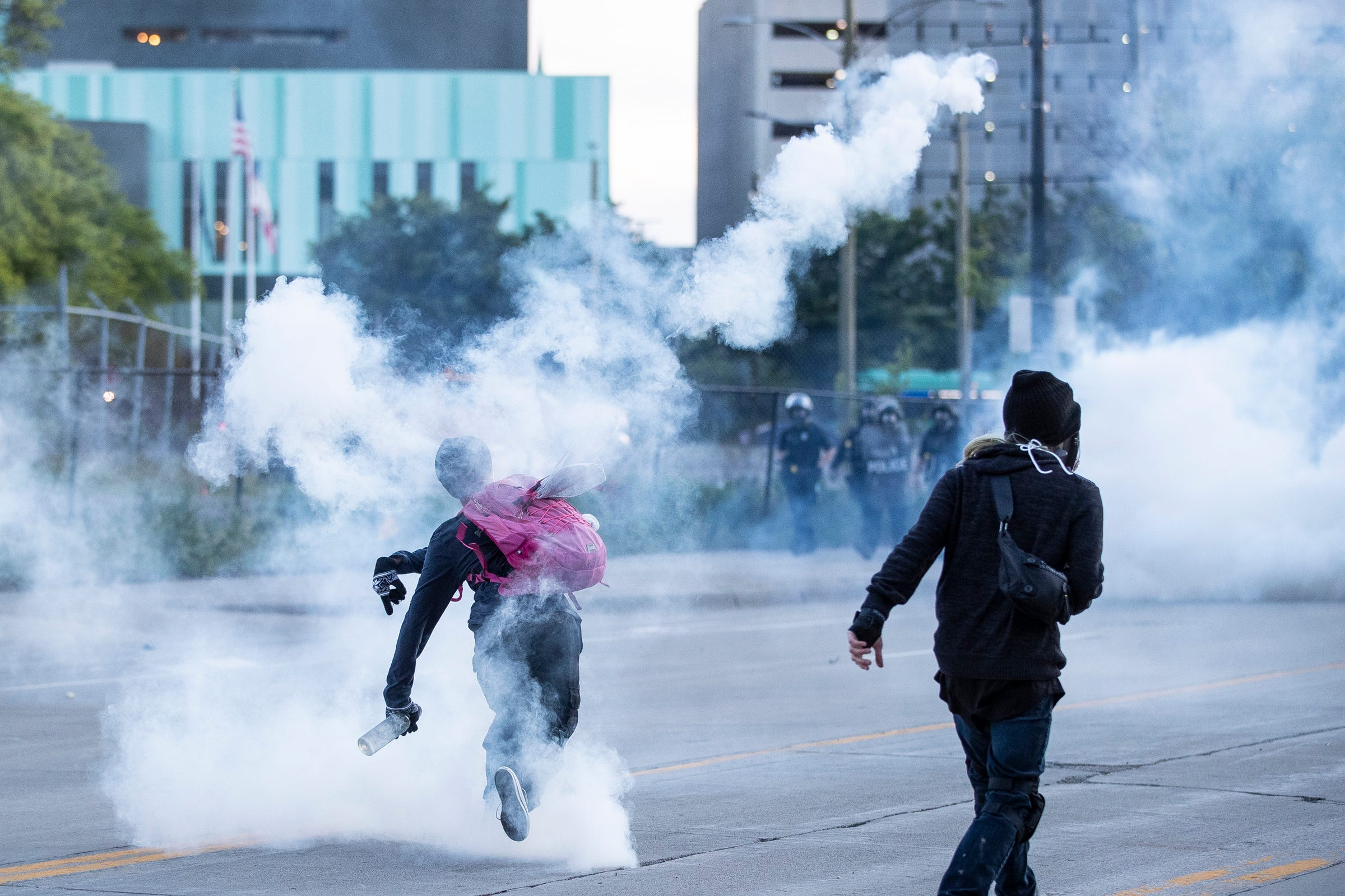 Protesters try to throw the tear gas can back at the Detroit Police officers on Michigan Avenue in Detroit, Sunday, May 31, 2020.