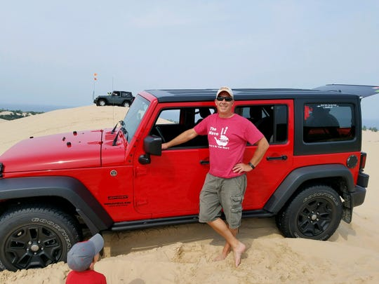 Mark Tuttle, 55, of Grandville, Michigan, has a secret vault in his 2016 Jeep Wrangler and now, he said, so do most of his friends. He is pictured here at Silver Lake Sand Dunes in 2017.