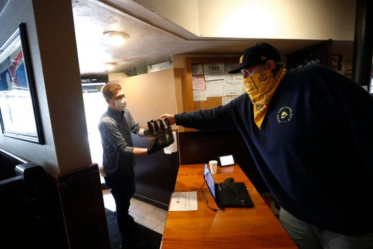 In this May 19, 2020, photo, Kyle Froelich, right, hands a customer a carryout six-pack of beer at Good Time Charley's in Ann Arbor, Mich.