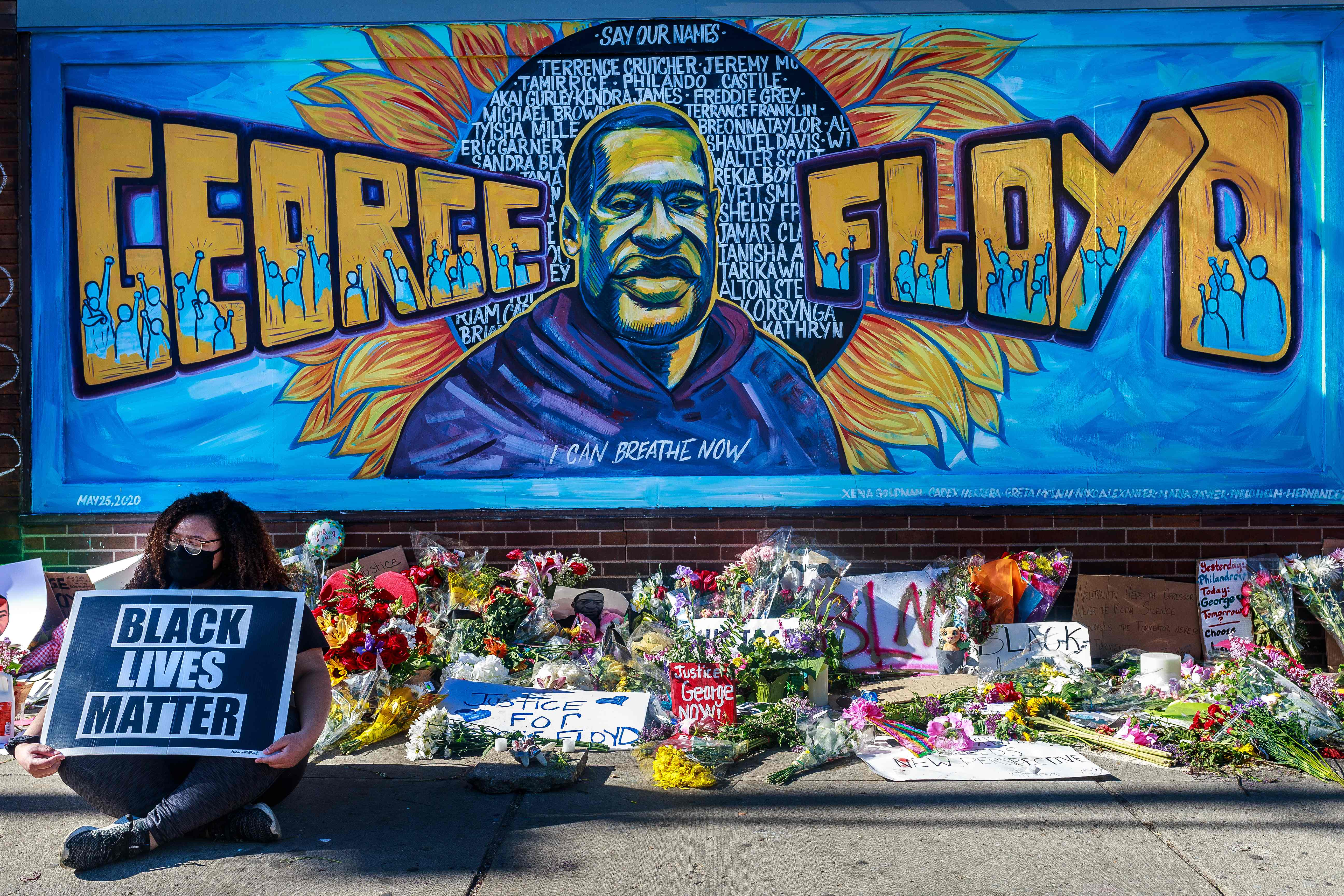 Flowers, signs and balloons are left near a makeshift memorial to George Floyd near the spot where he died while in custody of the Minneapolis police, on May 29, 2020 in Minneapolis, Minnesota. - Demonstrations are being held across the US after George Floyd died in police custody on May 25.