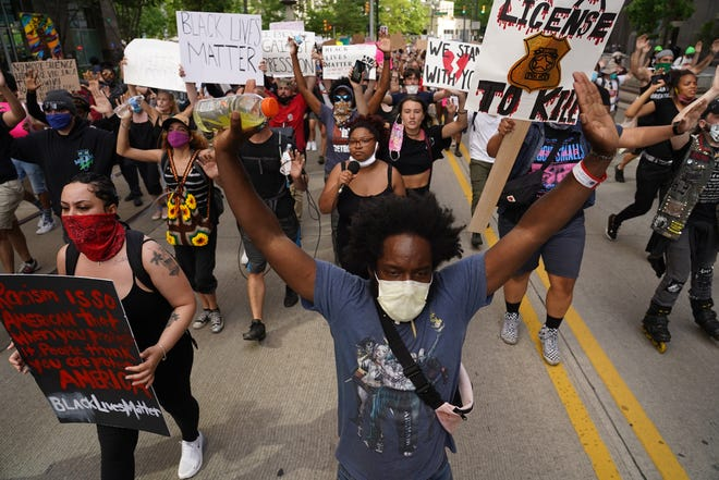 Tristan Taylor of Detroit leads a group of protesters along Woodward Avenue during the sixth day of protests against police brutality on Wednesday, June 3, 2020.