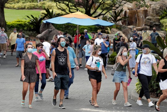Guests wearing masks stroll through SeaWorld as it reopened with new safety measures in place in Orlando, Fla. The park had been closed since mid-March to stop the spread of the new coronavirus.