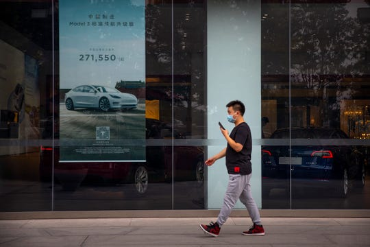 A man walks past a Tesla car showroom in Beijing, Thursday, June 11, 2020. China's auto sales surged 14.5% in May, a second straight month of growth.