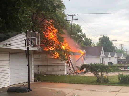 A wire downed during a storm Wednesday sets a tree on fire, which spreads to a garage in Grosse Pointe Woods.