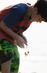 Tucker Eden, 10, of Boonville, Ind., cleans the moss off his lure while fishing with his granddad, Dave Wallace, at Boonville City Lake Tuesday evening, June 2, 2020. It was the duo's first trip fishing since the COVID-19 outbreak.
