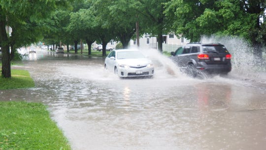 Two vehicles pass through flood waters on Military Road, between Hickory Road and the railroad crossing at about 6:40 p.m. on Wednesday, June 10 in Fond du Lac, Wisconsin.
