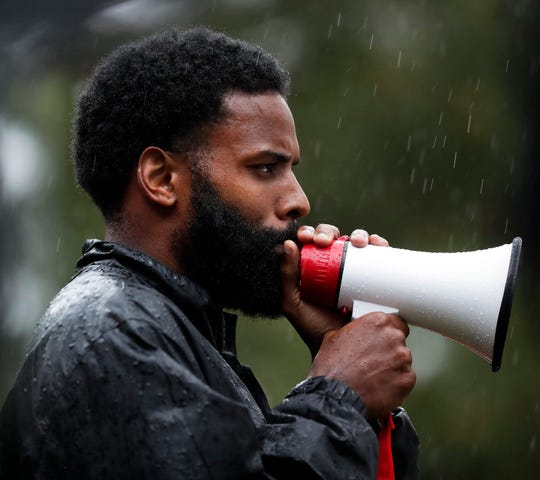 Tevin Taylor, who co-organized a protest in response to the killing of George Floyd in Minneapolis, speaks to about 100 people who marched throughout De Pere in the rain on June 10, 2020.