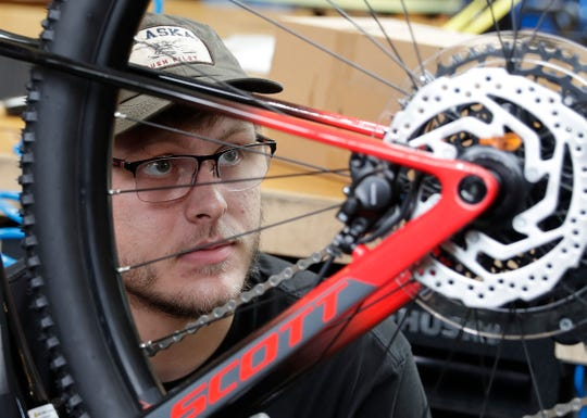 Nick Godwod, mechanic at Pete's Garage, checks the drivetrain of a bicycle brought in for repairs on June 10, 2020, in Green Bay, Wis.