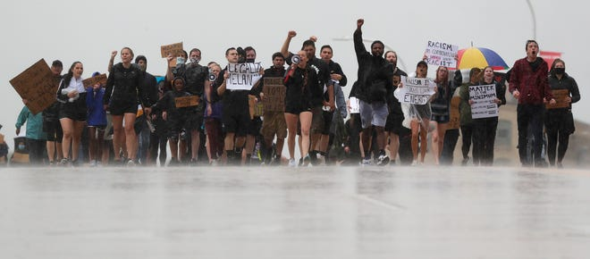 Protesters march across the Claude Allouez Bridge in De Pere to demand an end to police brutality during a rain storm on June 10, 2020.