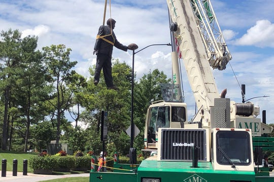A statue of former Carolina Panthers owner Jerry Richardson is removed from in front of the team's stadium in Charlotte, N.C., Wednesday, June 10, 2020.