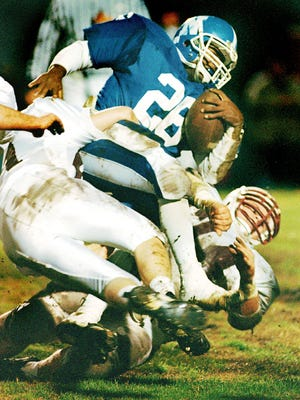 North Hardin fullback Erin Mansfield gets hauled to the ground by Henderson County defenders Kevin Ray, underneath, and Todd Duncan, left, during the 1996 first round playoff game in Radcliff Friday night.