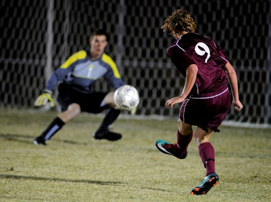 Henderson County Colonel Nick Gregory fires a shot on goal to Heath goalkeeper Ollie Douthitt for a score as the Henderson County Colonels play the Heath High School Pirates Monday evening in West Paducah for the state sub-sectional game.