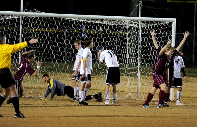 Henderson and Heath players react after the winning goal was scored by Demetrius Carter in overtime at Monday's soccer sub-sectional in Paducah.