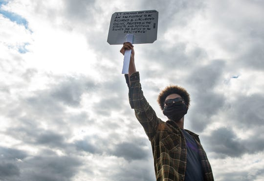 Iyad Abdi holds a sign during a peaceful protest at Old Hickory Mall and City Hall in Jackson, Tenn., on June 10, 2020. Abdi started a petition to remove the Confederate soldier statue at the Madison County Courthouse.