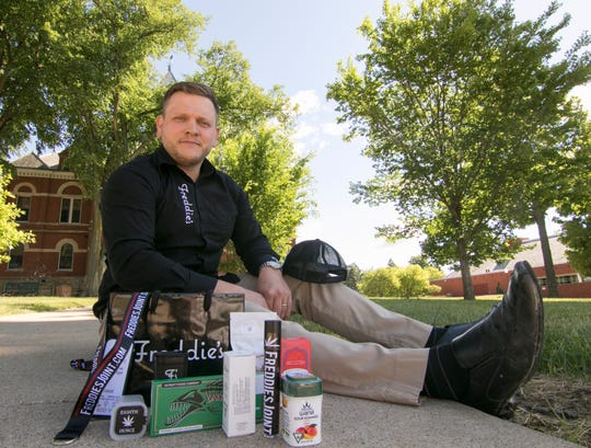 Brett Stephens, general manager of Freddie's, a cannabis dispensary near Clio, poses Thursday, June 11, 2020 with some of the products the company will delivery to customers in Livingston County.