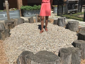 Mia Cooper, Head Start director, stands atop a rock pile for children's play at the Keystone Learning Academy in Louisville. The child care center reopens Monday.