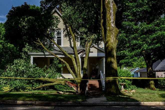 A tree that was toppled rests on a home in Mason on Wednesday, June 10, 2020, after a strong rain storm rolled through the area.
