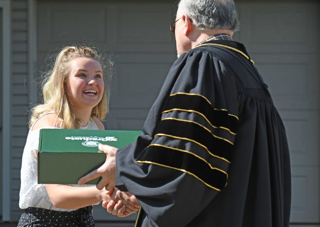 NCSC graduate Haley Shears shakes hands with Dorey Diab, president and CEO of North Central State College, during a makeshift graduation ceremony in her driveway last year.
