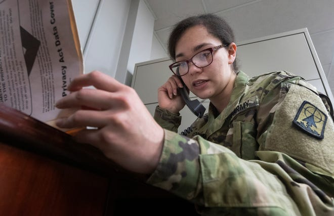 Spc. Kami Henning talks to a recently tested person about the results of their test for COVID-19.