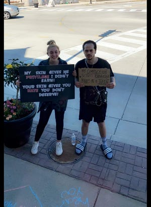 Kira Bannister is with her brother, Jordan, as they were chalking sidewalks June 8 to support the Black Lives Matter movement in downtown Menomonee Falls.