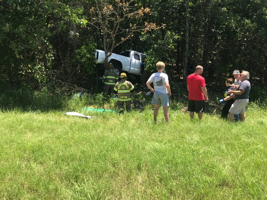 Emergency workers attempt to free a person from a pickup truck at an accident on the bypass.