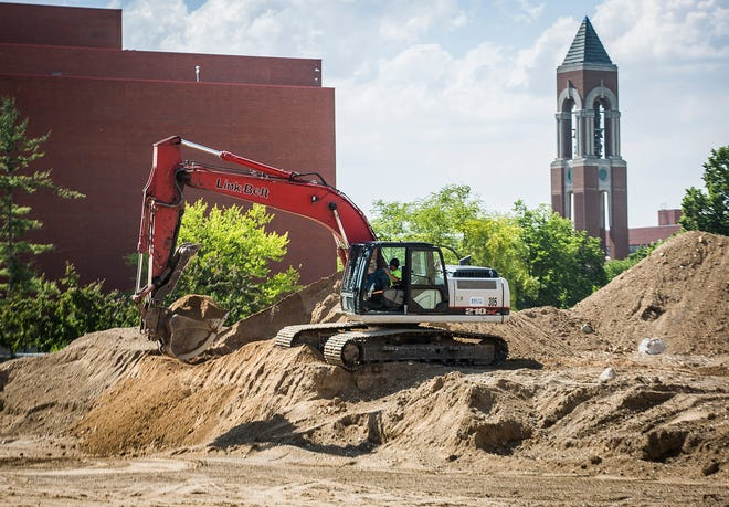 Construction crews work at the site of the former Emens Auditorium parking garage on Ball State's campus Thursday, June 11, 2020.