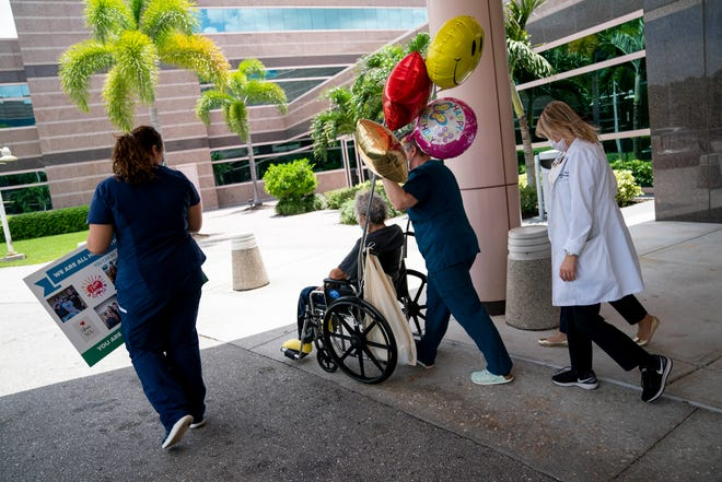 Hospital staff wheel Richard Czekanski to his wife's car after he was released form Physicians Regional Medical Center Pine Ridge in Naples on Thursday, June 11, 2020.