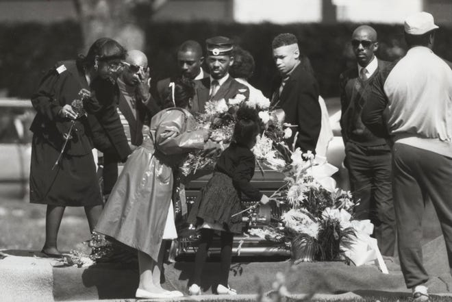 Teaneck 4/16/90 Mourners pay last respects at the graveside and place flowers on the casket of Phillip Pannell.