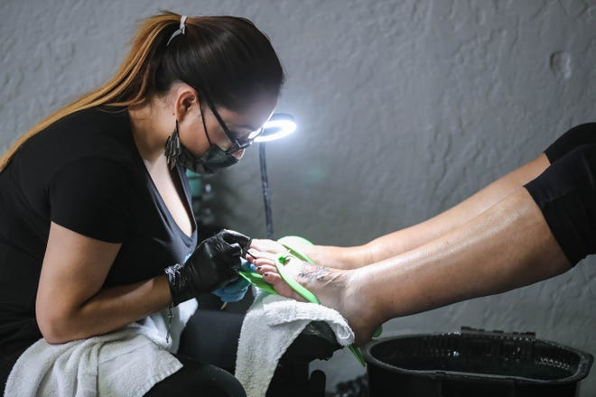 Yanitza Peres gives a pedicure to a customer while wearing a mask at Dazzle Nails in Las Cruces on Thursday, June 11, 2020.