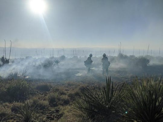 Smoke from the fire in the Sierra de las Uvas mountain range covers firefighters as they work to contain the blaze Tuesday, June 9, 2020.