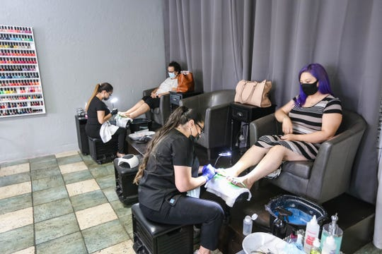 Yanitza Peres and Rubi Herrera give pedicures to customers while wearing masks at Dazzle Nails in Las Cruces on Thursday, June 11, 2020.