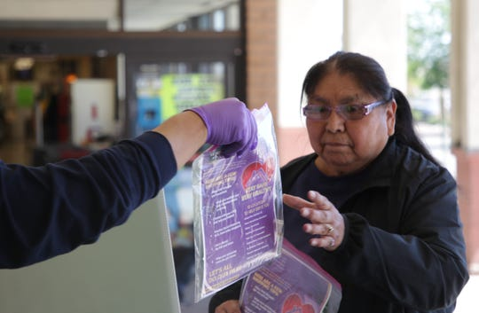 A community member receives personal safety kits from Navajo Nation Shopping Centers Inc. as part of the company's free refills of hand sanitizer on June 10 in Shiprock.