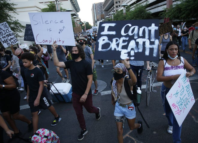 Protesters march against racial injustice in downtown Phoenix on June 10, 2020. People have been seeking justice for George Floyd, killed by police in Minnesota, and Dion Johnson, shot by an Arizona Department of Public Safety officer in Phoenix.