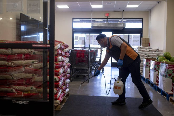 Jason Park sanitizes a carpet at the entrance during the grand opening of H Mart on June 11, 2020, in Mesa, Ariz.