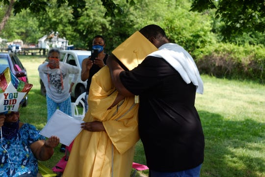 Cape Henlopen graduate Ashante' Custis hugs a family member while waiting for her diploma to arrive at her Rehoboth home. The Class of 2020 had their diplomas hand-delivered by 100 district staff members Wednesday, June 10, 2020.