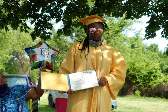 Cape Henlopen graduate Ashante' Custis holds her diploma outside her Rehoboth home on Wednesday, June 10, 2020. The Class of 2020 had their diplomas hand-delivered by 100 district staff members.