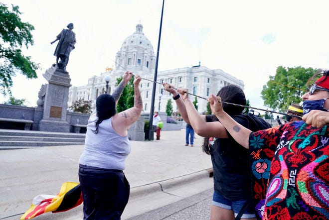 Activists bring down the Christopher Columbus statue in front of the Capitol, Wednesday, June 10, 2020, in St. Paul, Minn. A rope was thrown around the 10-foot bronze statue and it was pulled off its stone pedestal. The protesters included Dakota and Ojibwe Indians who consider Columbus as a symbol of genocide against Native Americans. State Patrol troopers in helmets stood by at a distance but did not try to stop the protesters. (Leila Navidi/Star Tribune via AP)