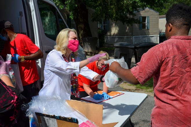 Karen Moore helps distributes food at the mobile site on Wednesday.