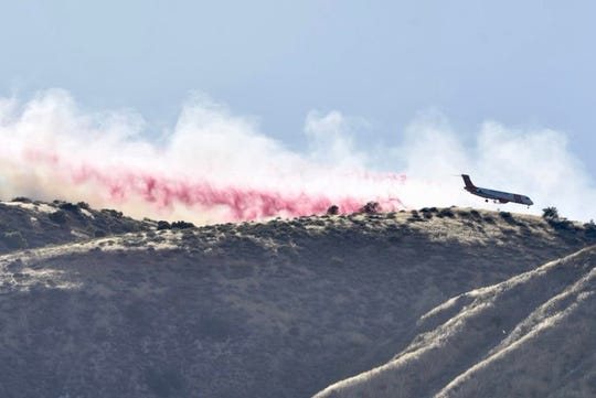 An aerial air tanker drops water on a ridge above the Lime Fire near Lake Piru Wednesday.