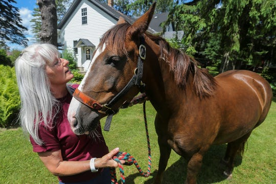 Denice Feit pets her mustang, Nala, on Friday, June 5, 2020, at a farm outside of Knowlton, Wis. Feit won the chance to adopt Nala after writing an essay for a contest set up by a horse trainer in Florida.