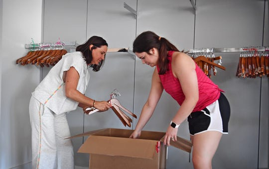 The Shoe Closet owner Becky Lindemann and her daughter-in-law, Laura Lindemann, pack up hangers Thursday morning. The womens apparrel store has closed after 36 years in business.