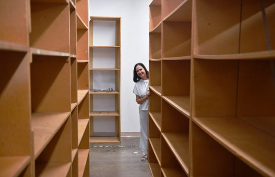 Becky Lindemann, owner of The Shoe Closet, looks down one of several rows of empty shelves which once held thousands of pairs of womens shoes. Lindemann is retiring and closing her business after 36 years.